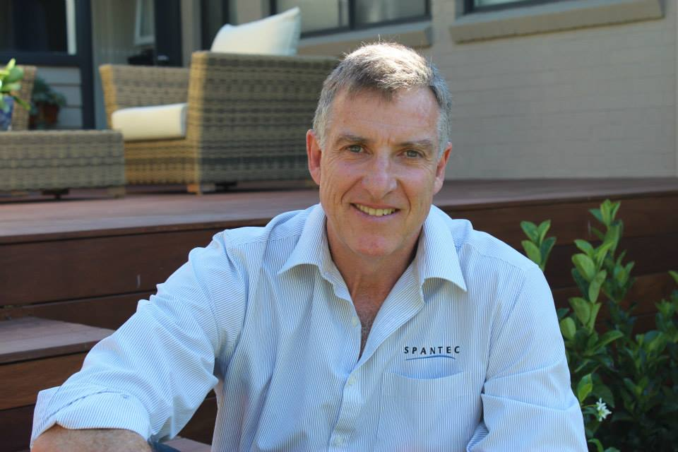 Spantec Director, Roy Beaumont smiling, witting on a deck constructed using Spantec deck frame.