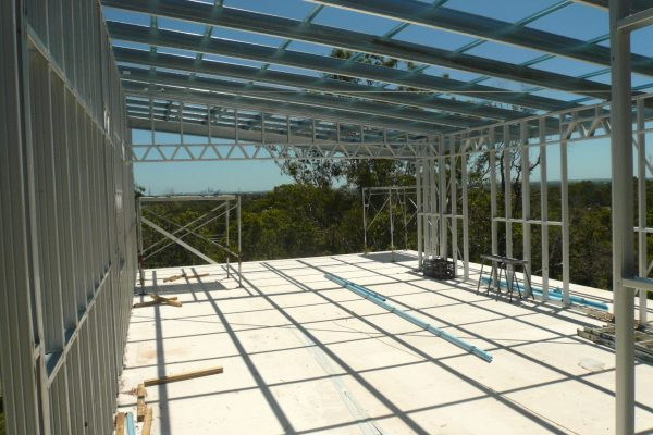 Boxspan skillion roof frame on steel wall framing on a steeply sloped site