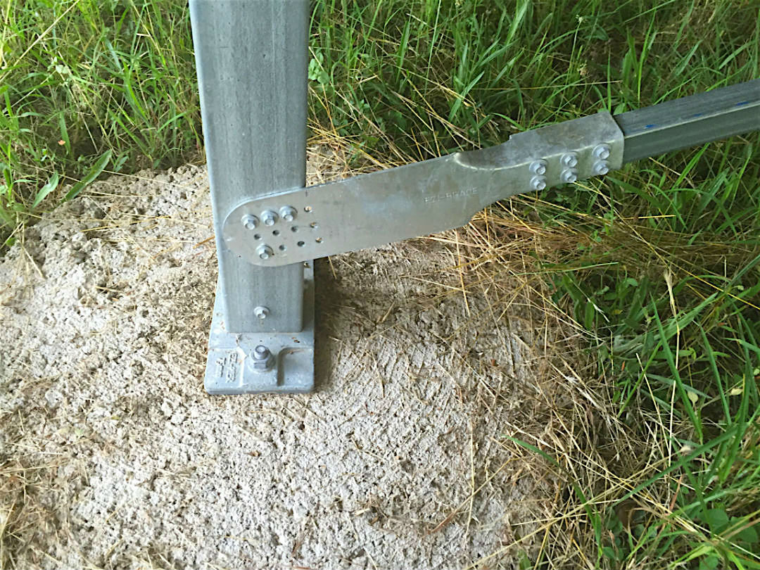 An Ezibrace Paddle fixed to an SHS post with screws above an Ezipier base on a concrete round footing