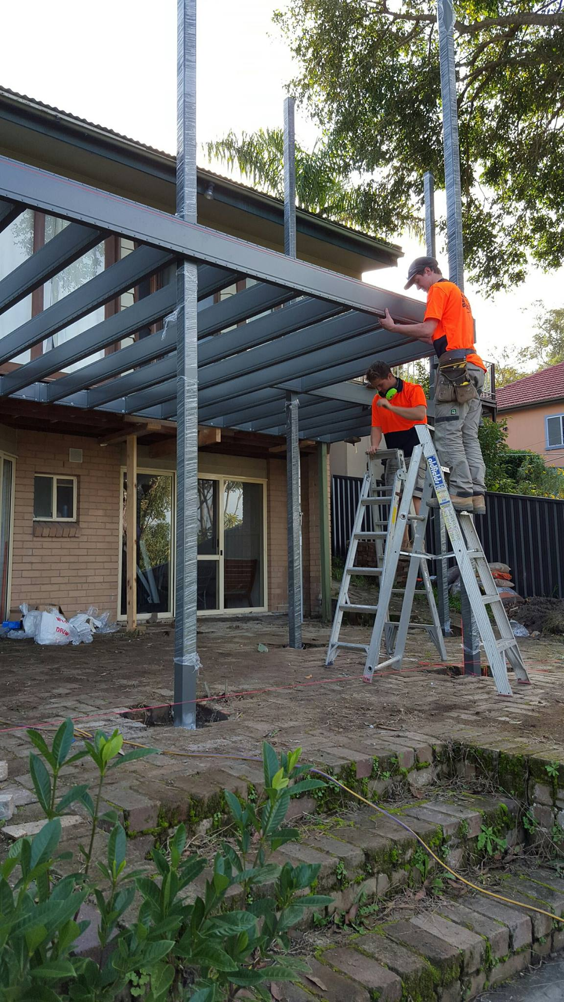Powder coated two-story deck frame installation on existing home