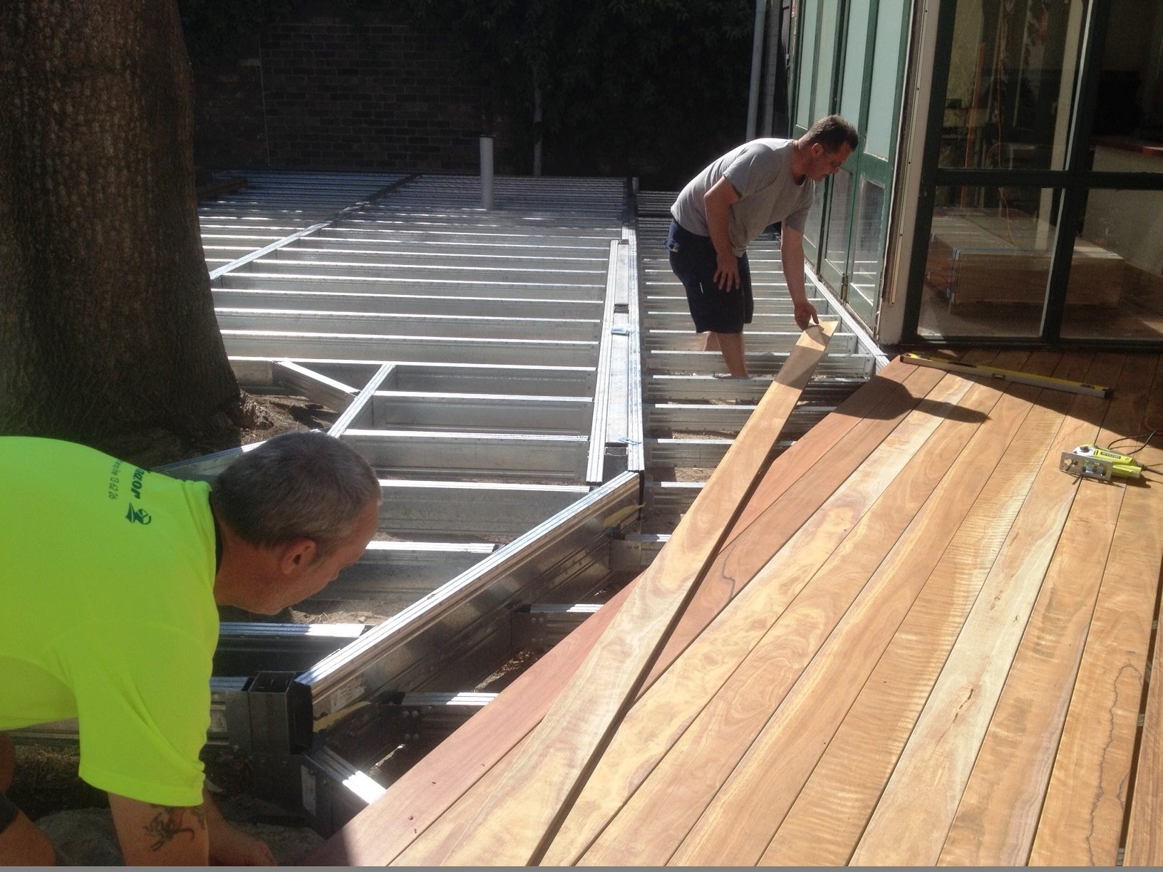 Installation of wide decking boards on a commercial deck at a pub outdoor dining area